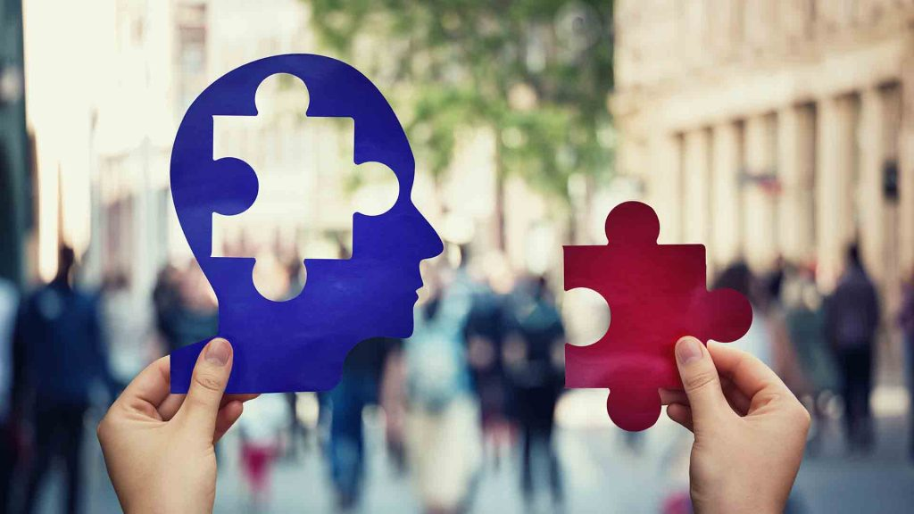An outline of a head in someones left hand, missing a jigsaw puzzle piece shape. The jigsaw piece is in the same persons right hand