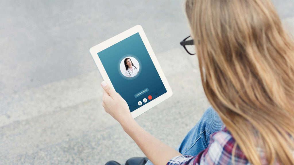 A young woman attempting to connect to her telepsychiatry appointment on a tablet