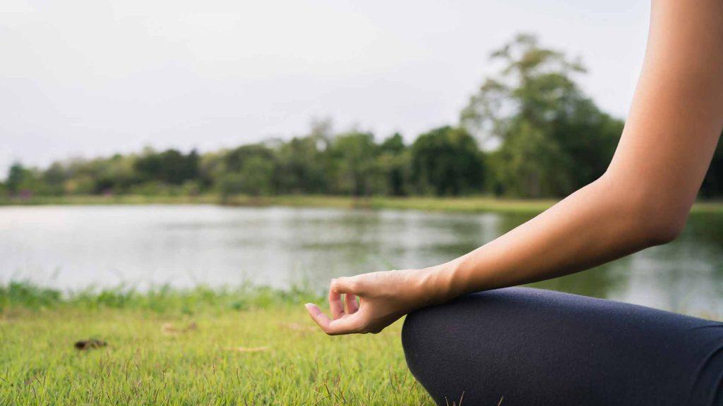 person meditating at the shore of a lake!